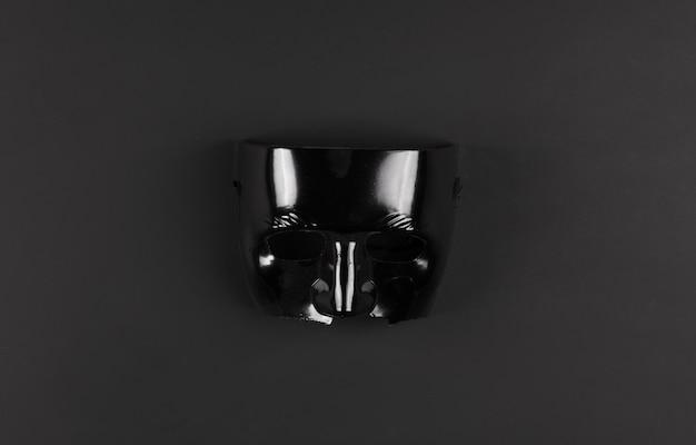 Czarna maska kryminalna na czarnym tle