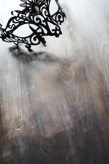 Czarna maska na drewnianym tle z miejscem na tekst