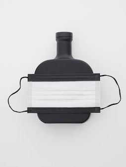 Czarna maska ochronna na twarz z butelką rumu na białym tle.