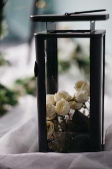 Czarna metalowa lampa z białymi różami, świecą i kwiatami na jasnym tle, wystrój domu,
