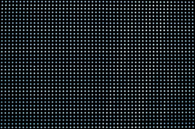 Czarna metalowa siatka z wieloma okrągłymi otworami. tło siatki.
