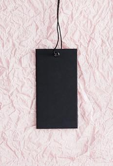 Czarna metka odzieżowa na rumianym różowym papierze tle zrównoważonej mody i koncepcji etykiety marki