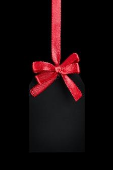 Czarna metka z czerwoną kokardą na czarnym tle na białym tle
