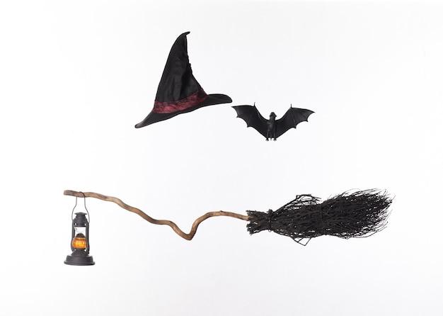 Czarna miotła i kapelusz czarownicy na białym tle