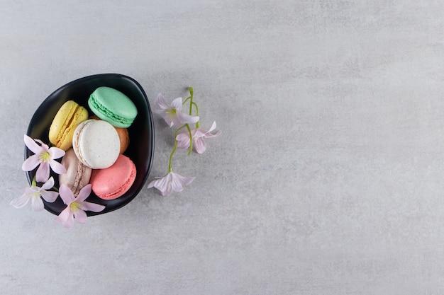 Czarna miska kolorowych słodkich makaroników z kwiatami na kamiennym stole.