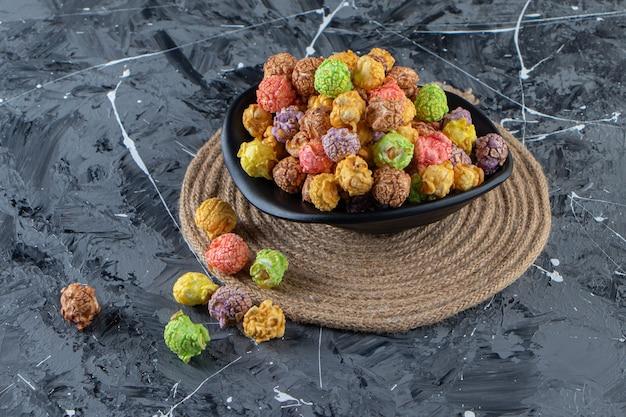 Czarna miska kolorowych smacznych popcornów na marmurowej powierzchni.