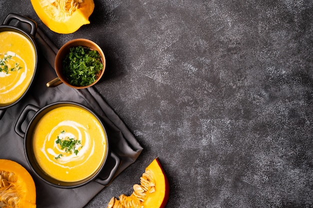 Czarna miska z dyniową jesienną zupą. wegańska pyszna, kremowa zupa z mlekiem kokosowym. widok z góry. ciemne tło.