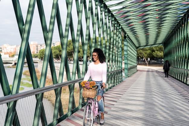 Czarna młoda kobieta jedzie rocznika bicykl