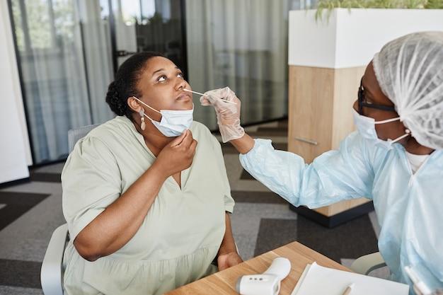 Czarna młoda kobieta pozwalająca lekarzowi pobrać wymaz z nosa w celu pobrania próbki do testu na covid