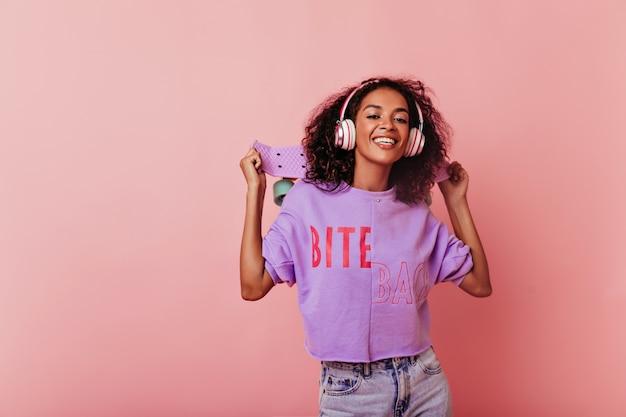Czarna młoda kobieta stojąca w pewnej pozie z deskorolką. wspaniałe kręcone afrykańskie dziewczyny w słuchawkach na pastelowym tle w studio.