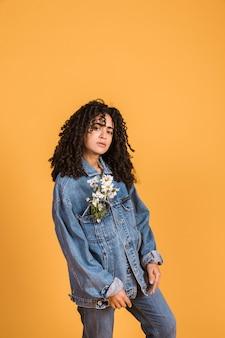 Czarna młoda kobieta z stokrotką kwitnie w kurtki kieszeni