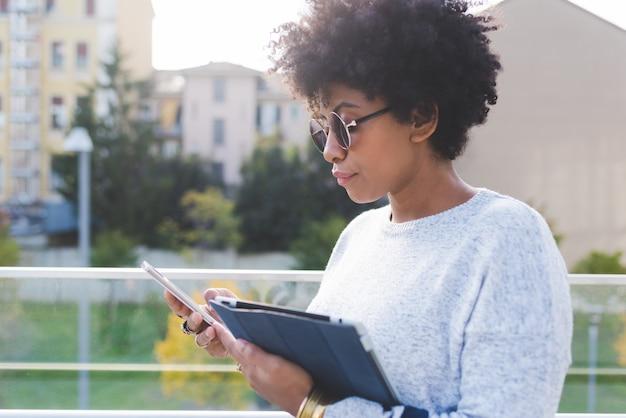 Czarna młoda kobieta z urządzeniami elektronicznymi