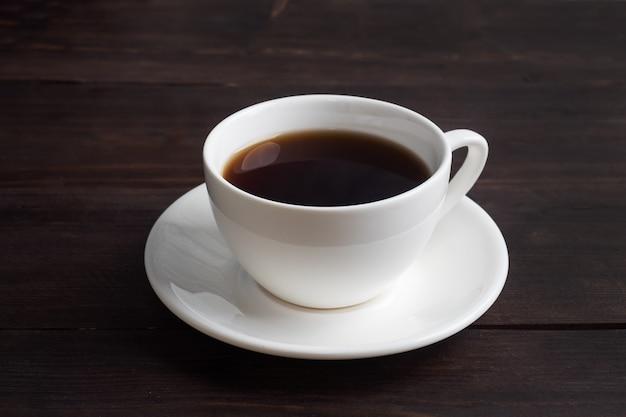 Czarna mocna kawa espresso w białej ceramicznej filiżance. drewniane ciemne.