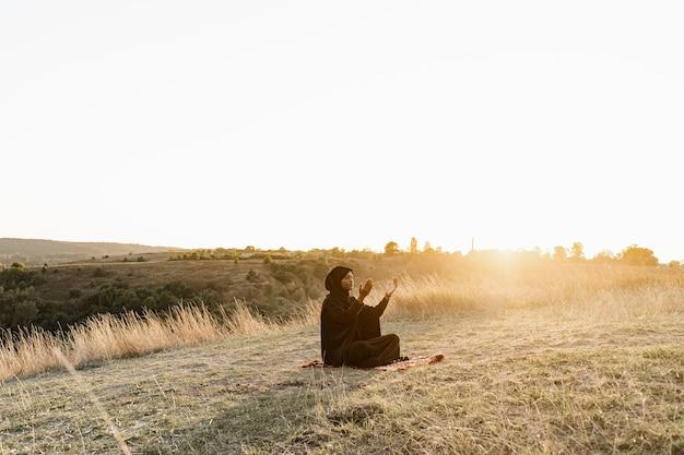 Czarna muzułmanka modli się do allaha o zachodzie słońca. solat tradycyjna modlitwa do boga na dywanie.