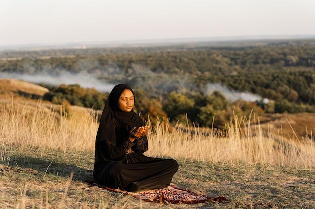 Czarna muzułmanka modli się na dywanie. solat modlący się na pięknym wzgórzu. salah tradycyjna modlitwa.