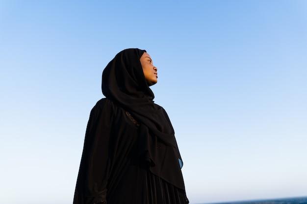 Czarna muzułmanka ubrana w czarną szatę na niebieskim tle. religia islamska. świętujemy ramadan.