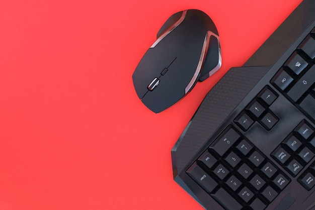 Czarna mysz, klawiatura odizolowywająca na czerwonym tle, odgórny widok. tło płaskie świeckich graczy.