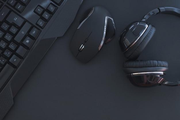Czarna mysz, klawiatura, słuchawki są izolowane na ciemnym tle, widok z góry. tło płaskie świeckich graczy.