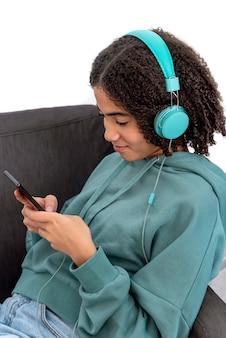 Czarna nastolatka w ubranie, przeglądanie smartfona i słuchanie muzyki, odpoczywając w fotelu w domu