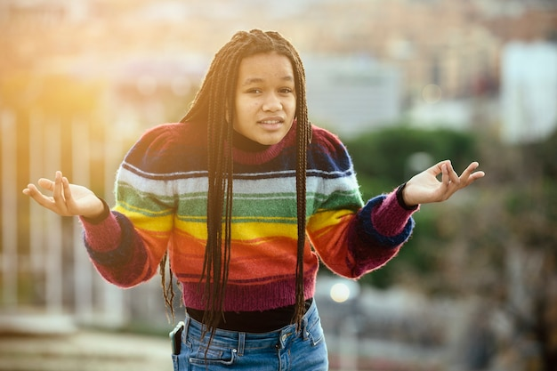 Czarna nastolatka z zaplecionymi włosami z wyrazem zmieszania i niewiedzy, w mieście