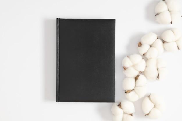 Czarna okładka książki i bawełniane kwiaty na szarym tle