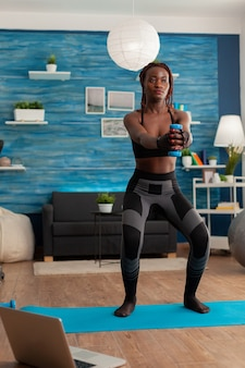 Czarna osoba skoncentrowała się na wykonywaniu przysiadów z hantlami z wyciągniętymi ramionami, ze stopami na macie do jogi w domu w salonie, aby wzmocnić mięśnie, po szkoleniu online na temat zdrowego stylu życia.