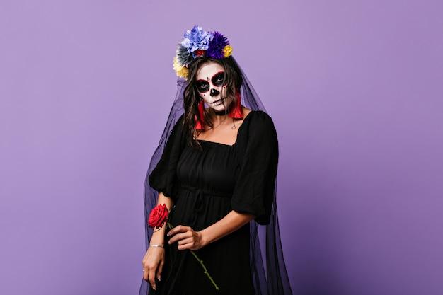 Czarna panna młoda trzyma czerwoną różę. portret modelki z przerażającym makijażem na halloween.