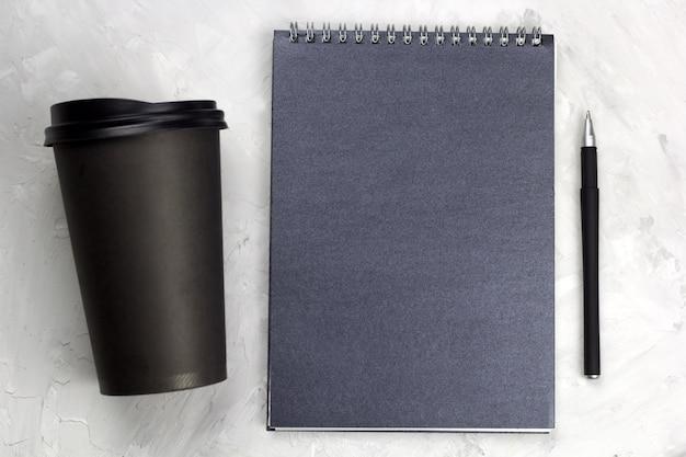 Czarna papierowa filiżanka kawy iść czarny notatnik i pióro