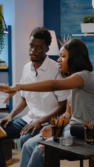 Czarna para artystyczna opowiadająca o technice rysunkowej w pracowni warsztatowej. kobieta i mężczyzna pochodzenia afroamerykańskiego pracujący nad udanym innowacyjnym arcydziełem do projektowania wazonów