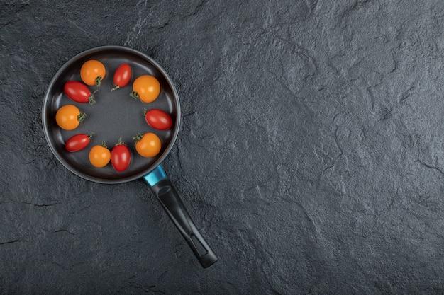 Czarna patelnia pełna pomidorków koktajlowych. wysokiej jakości zdjęcie