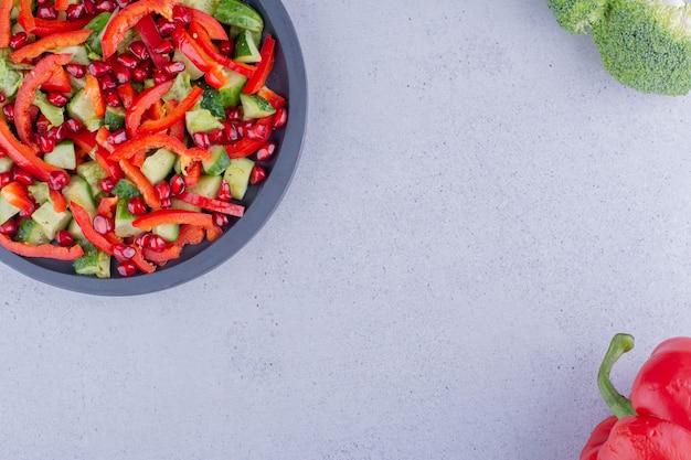 Czarna patelnia z sałatką jarzynową obok papryki i brokułów na marmurowym tle. zdjęcie wysokiej jakości