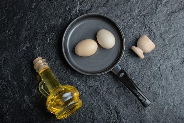 Czarna patelnia zawierająca surowe jajko i butelkę oleju na białym tle.