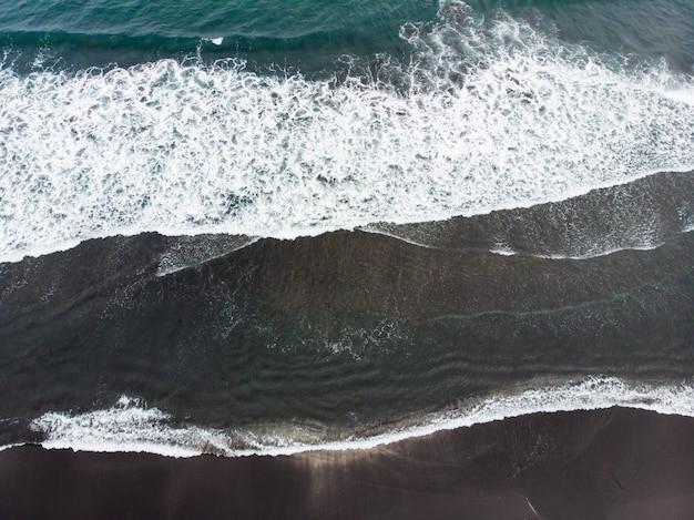 Czarna piaszczysta plaża reynisfjara i góra reynisfjall z cyplu dyrholaey na południowym wybrzeżu islandii.