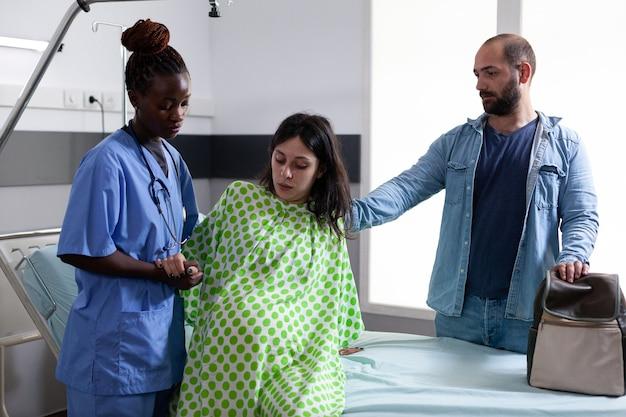 Czarna pielęgniarka położnicza pomagająca kobiecie w ciąży