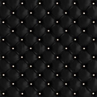 Czarna pikowana tekstura sofy ze złotymi guzikami.
