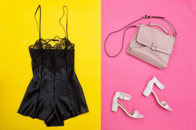 Czarna piżama z koronką, różową torbą i białymi butami. jasno różowo-żółte tło