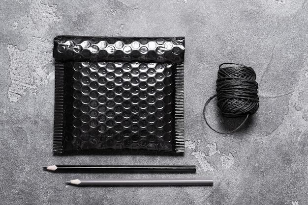 Czarna plastikowa bąbelkowa koperta na szarym tle