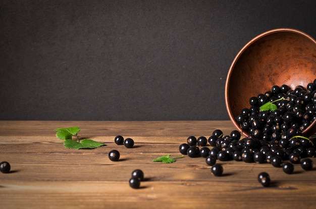 Czarna porzeczka na drewnianym stole z gałązką liści