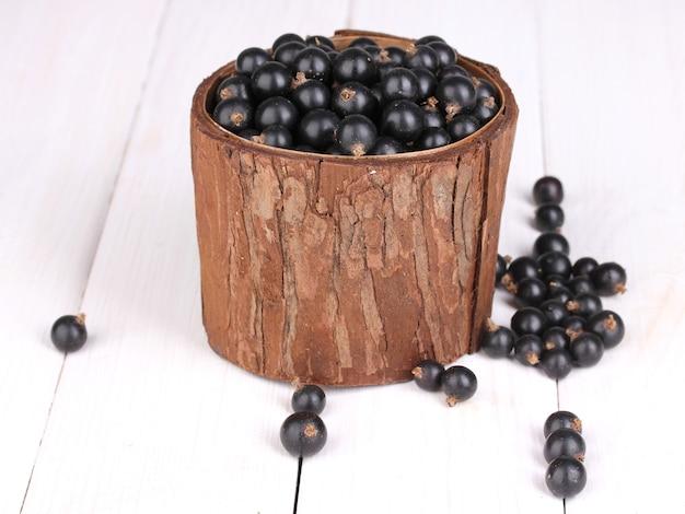 Czarna porzeczka w drewnianym kubku na drewnianym stole