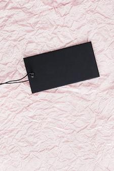 Czarna pozioma metka z ceną na różowym tle papieru
