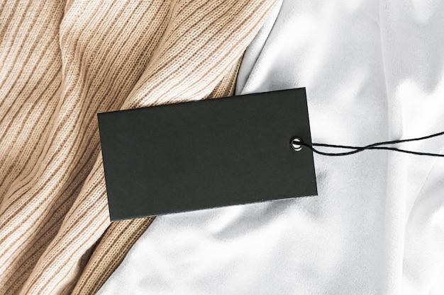 Czarna pozioma metka z ceną na tle luksusowej tkaniny