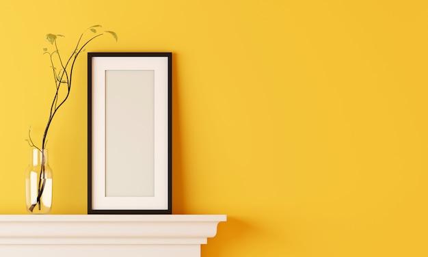 Czarna pusta ramka na żółtej ścianie pokoju ma wazon z kwiatami umieszczony na kominku