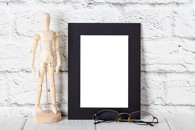 Czarna ramka na drewnianej półce lub stole. makieta z miejsca na kopię