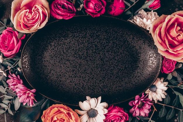 Czarna ramka na talerz ozdobiona pięknymi letnimi kwiatami. różowe róże i białe stokrotki widok z góry, stonowane zdjęcie.