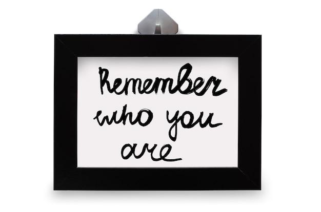 Czarna ramka na zdjęcia. napis pamiętaj, kim jesteś. na białym tle