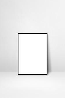 Czarna ramka na zdjęcia oparta na białej ścianie. pusty szablon makiety