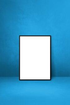 Czarna ramka na zdjęcia oparta na niebieskiej ścianie. pusty szablon makiety