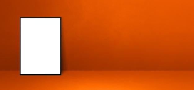 Czarna ramka na zdjęcia oparta na pomarańczowej ścianie. pusty szablon makiety. baner poziomy