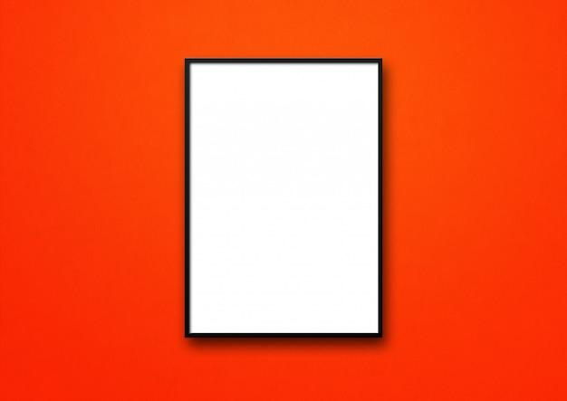 Czarna ramka na zdjęcia wisząca na czerwonej ścianie. pusty szablon makiety