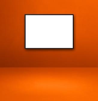 Czarna ramka na zdjęcia wisząca na pomarańczowej ścianie. pusty szablon makiety